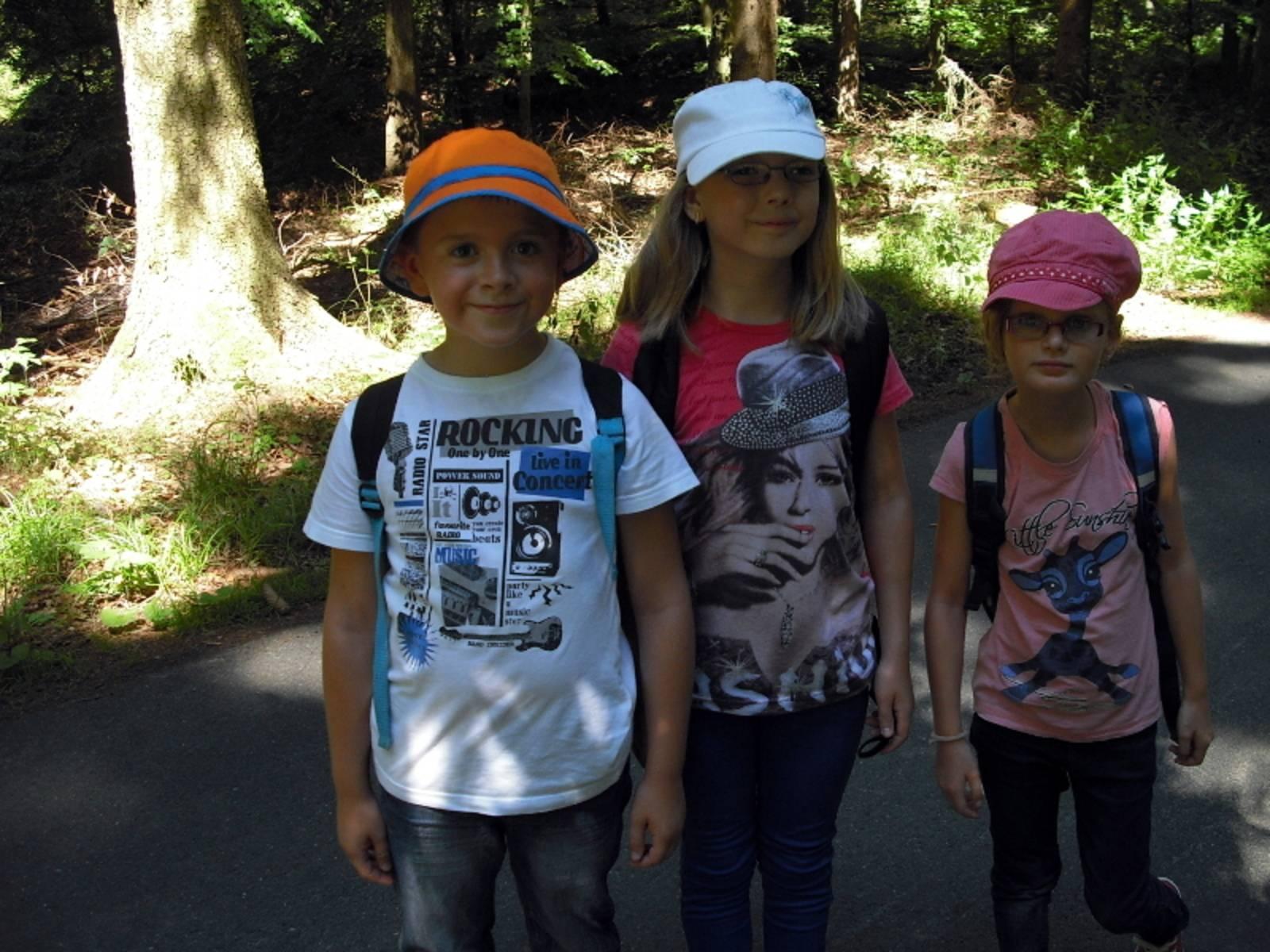 Ein Junge und zwei Mädchen auf einer Wanderung im Wald.