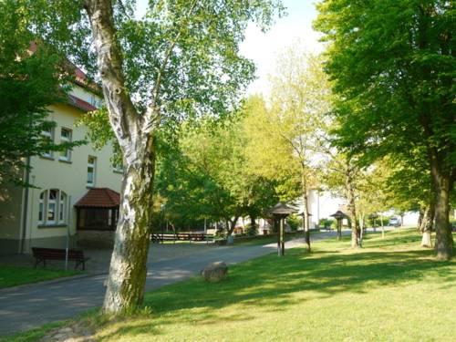 Gelbes Haus mit asphaltiertem Weg davor. Sowie Grünfläche mit Baumbestand.
