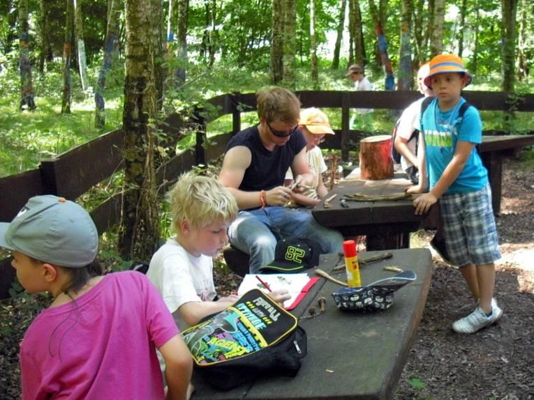 Kinder sitzen im Wald an Tischen