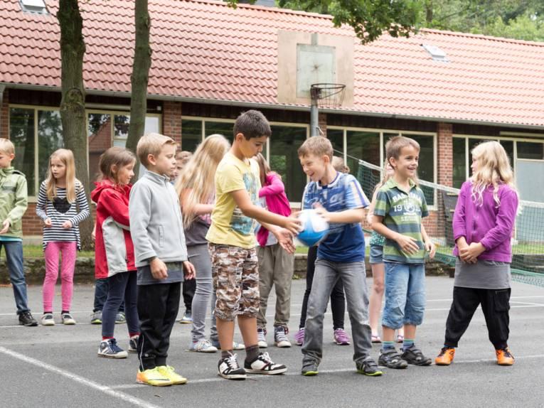 Kinder üben mit einem Rugby-Ei das Pässe werfen.