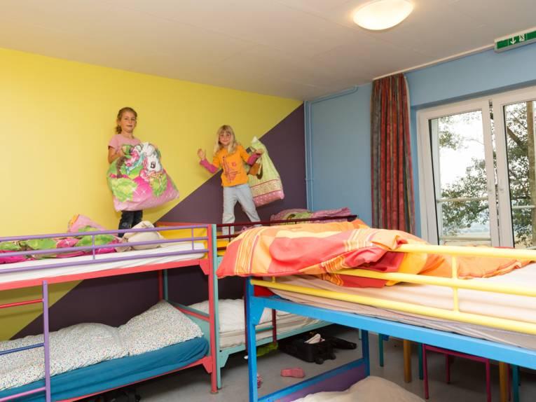 Zwei Mädchen stehen auf Hochbetten und beziehen ihr Bett.