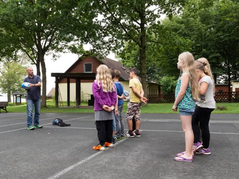 Ein Mann mit einem Rugby-Ei steht vor einer Gruppe mit Kindern.