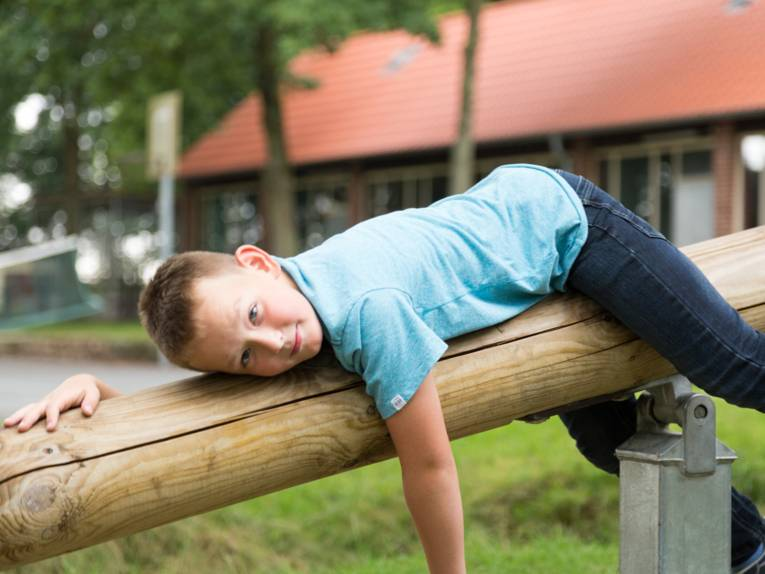 Junge liegt auf einer Wippe und ruht sich aus.