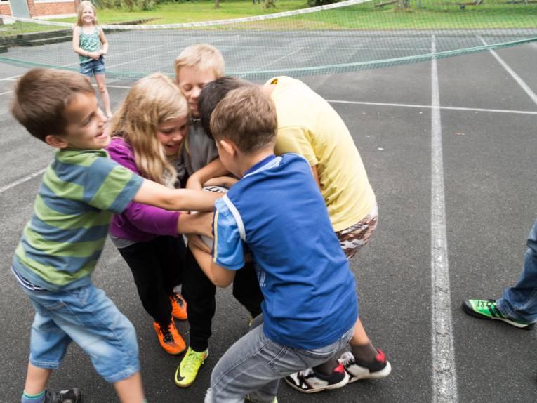 """Jungen und Mädchen """"kämpfen"""" um ein Rugby-Ei."""