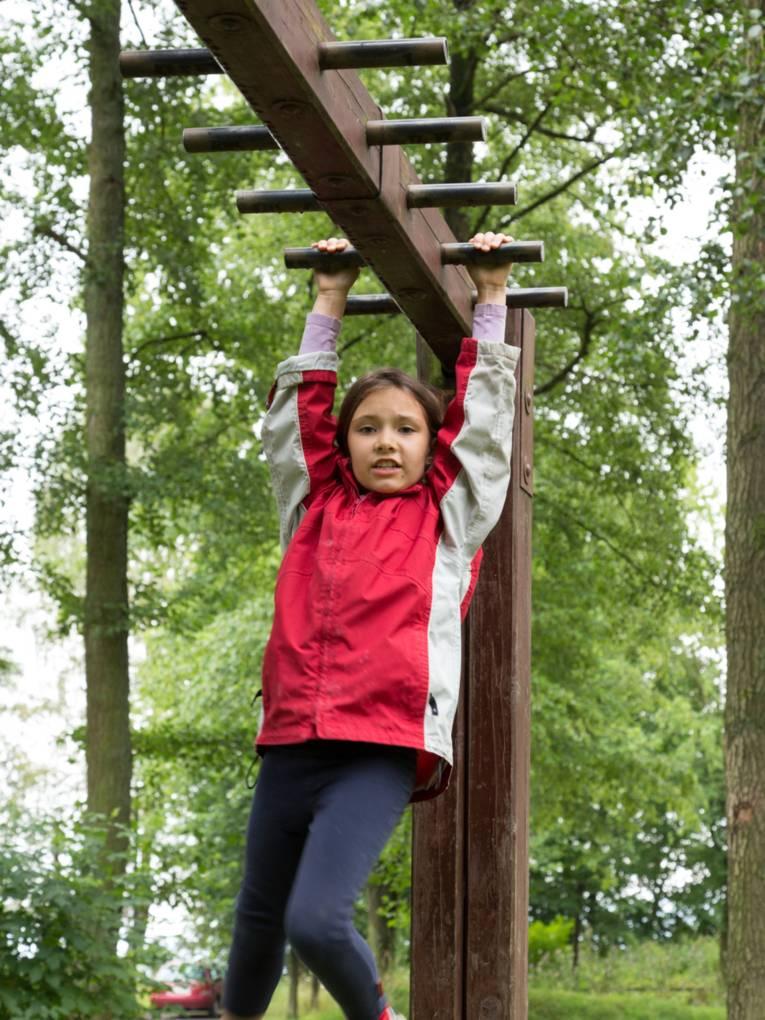 Ein Mädchen hangelt sich an einem Gerüst entlang.