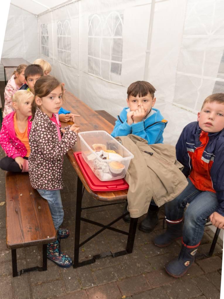 Kinder sitzen in einem Partyzelt und essen Muffins.