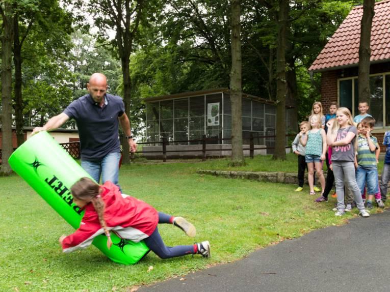 Ein Mädchen schmeisst sich an einen Rugby-Dummy.