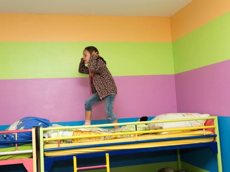 Ein Mädchen steht auf einem Hochbett.