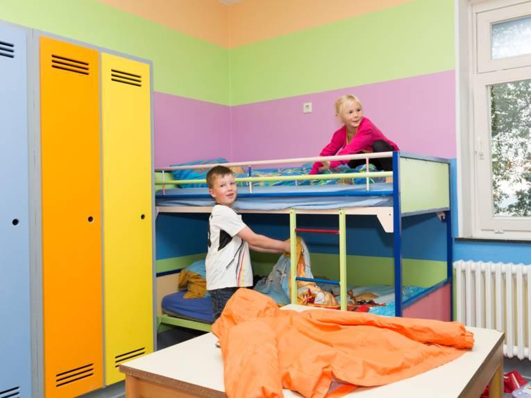 Kinder beziehen ihre Betten.